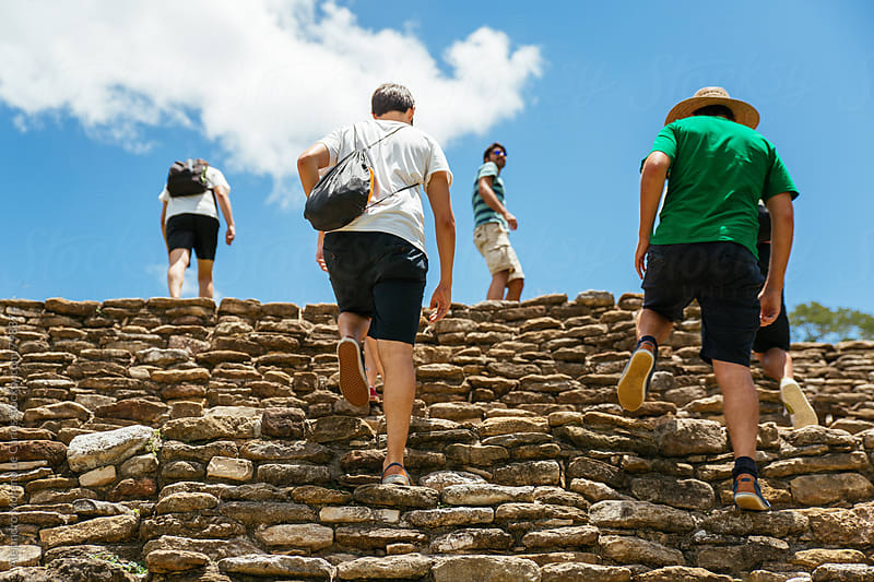 Four men climbing the steps of ancient pre-columbian ruin on a sunny day during their vacation travel by Alejandro Moreno de Carlos for Stocksy United