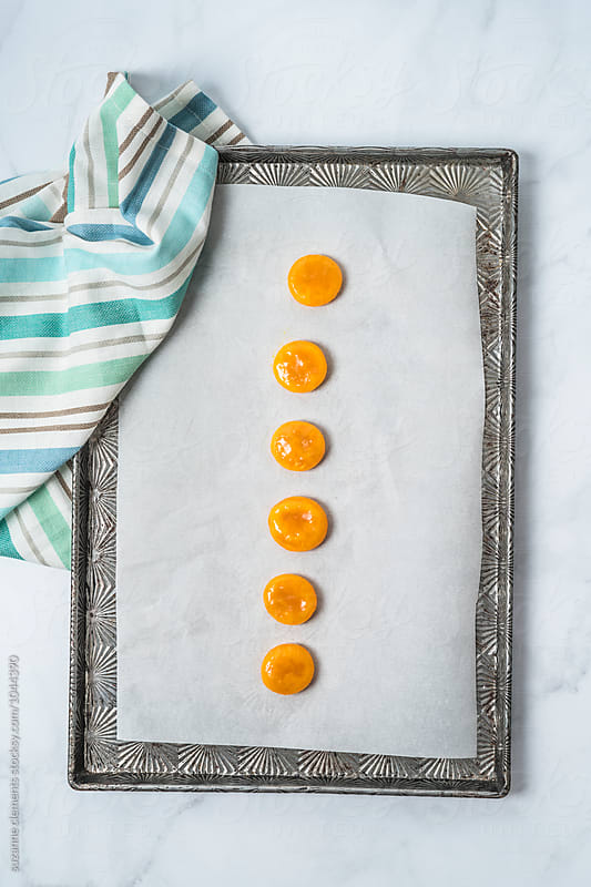 Cured Egg Yolks on a Baking Sheet to be Dried by suzanne clements for Stocksy United