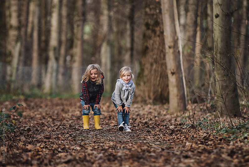 cheeky little boy and girl standing in autumnal forest by Leander Nardin for Stocksy United