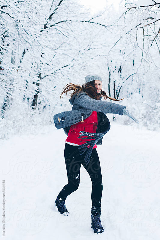 Girl throwing a snowball by Borislav Zhuykov for Stocksy United