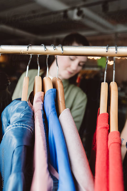 Young woman looking through clothes on racks by Carey Shaw for Stocksy United