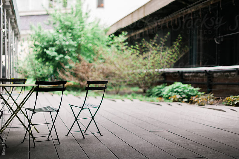 Cafe Chairs and a Table in a Shaded Patio by Briana Morrison for Stocksy United