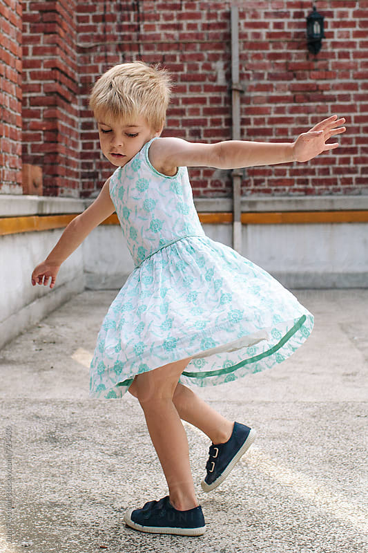 Blonde boy child spins around in a pretty dress. by Julia Forsman for Stocksy United