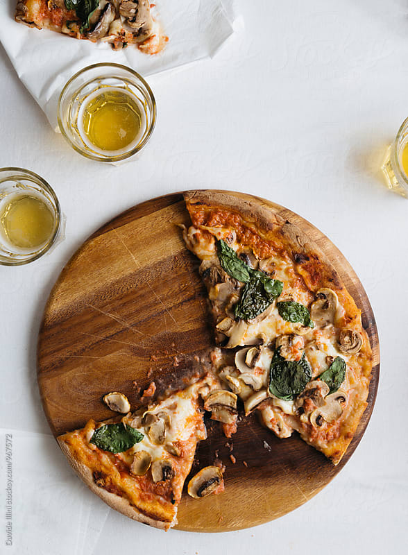 Pizza with mushrooms and basil by Davide Illini for Stocksy United