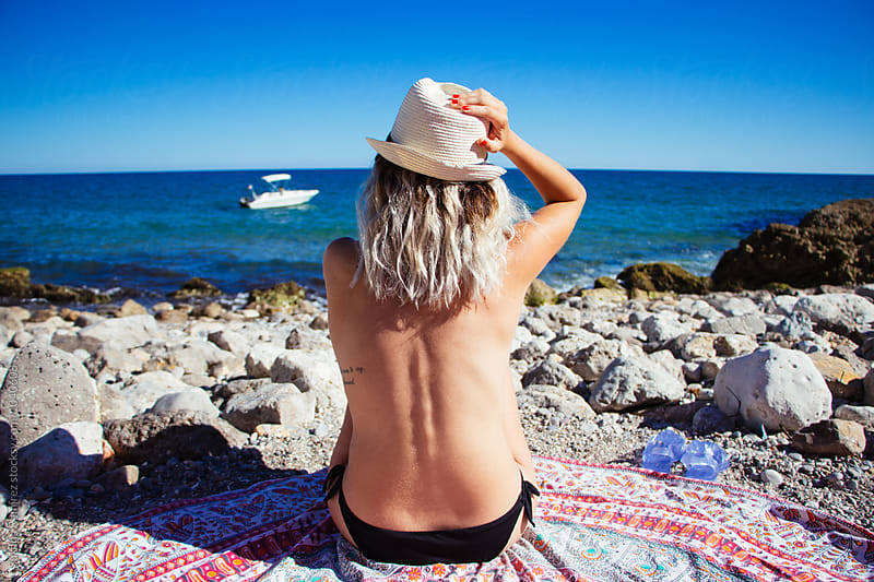 Portrait of relaxed woman sunbathing in a paradisiac cove by Susana Ramírez for Stocksy United