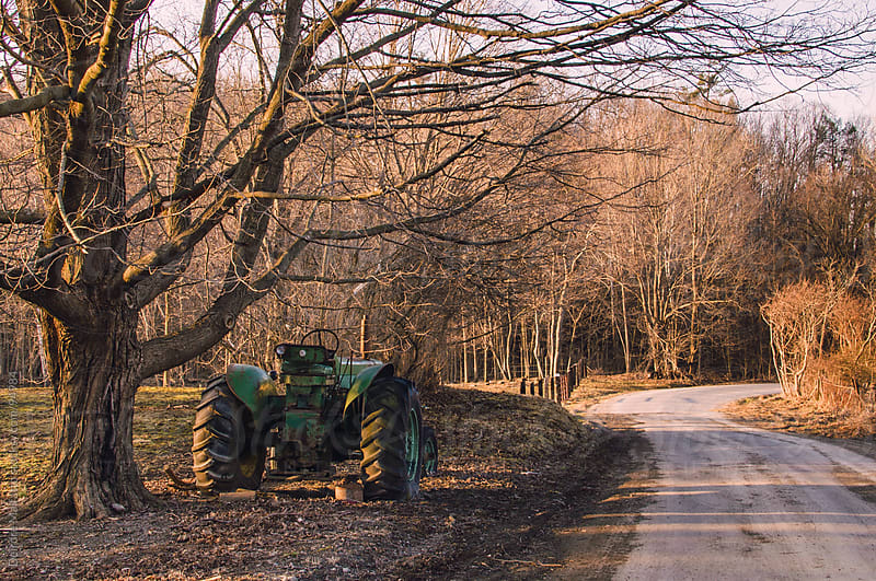 green tractor parked under a tree by a country road by Deirdre Malfatto for Stocksy United