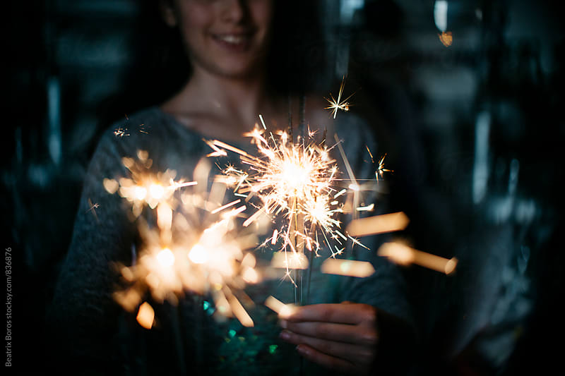 Woman holding sparklers, several of them creating heart shaped blur by Beatrix Boros for Stocksy United