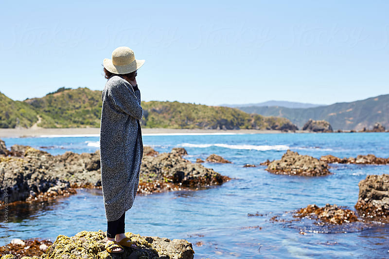 Woman in hat standing on rocks and looking away by Martí Sans for Stocksy United