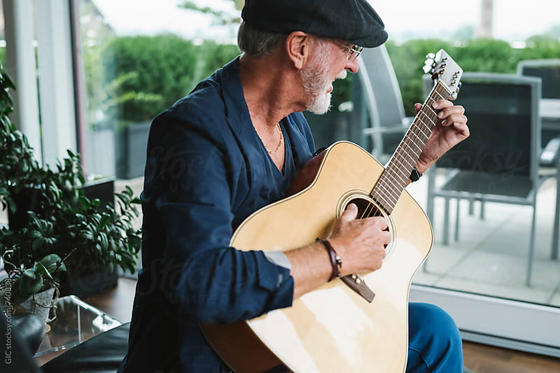 Happy active senior man playing a guitar at home by Simone Becchetti for Stocksy United