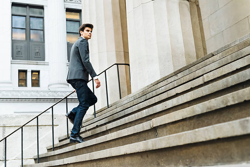 Businessman walking on the stairs by Simone Becchetti for Stocksy United