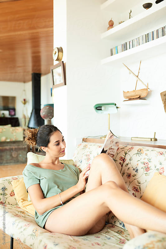 Beautiful brunette with bare legs reading book on sofa by Guille Faingold for Stocksy United