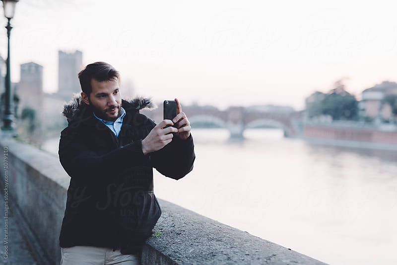 Man holding mobile phone during a cold evening by Good Vibrations Images for Stocksy United