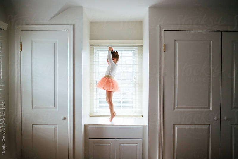 little girl doing ballet in a tutu on a window seat by Meaghan Curry for Stocksy United