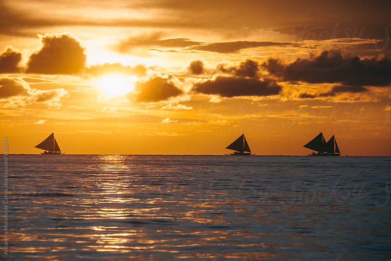 Sailboats at sunset by Alejandro Moreno de Carlos for Stocksy United