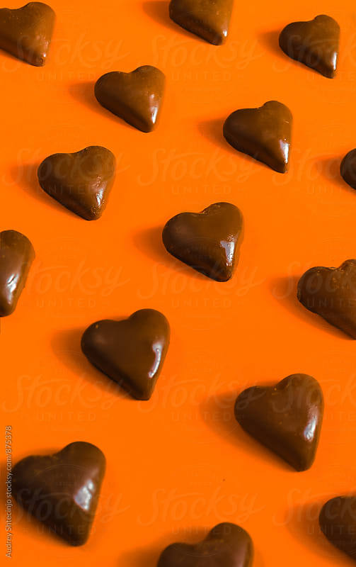 Chocolate hearts on orange background by Marko Milanovic for Stocksy United