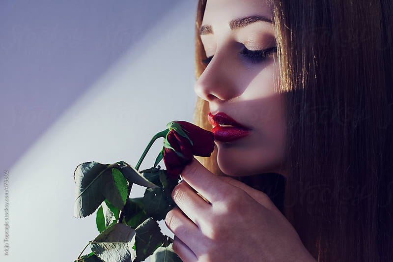 Young woman with red lipstick holding a red rose by Maja Topcagic for Stocksy United
