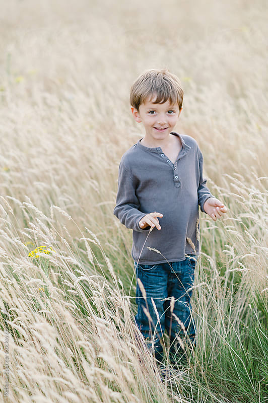Portrait of a cute child in a rural setting by Rebecca Spencer for Stocksy United