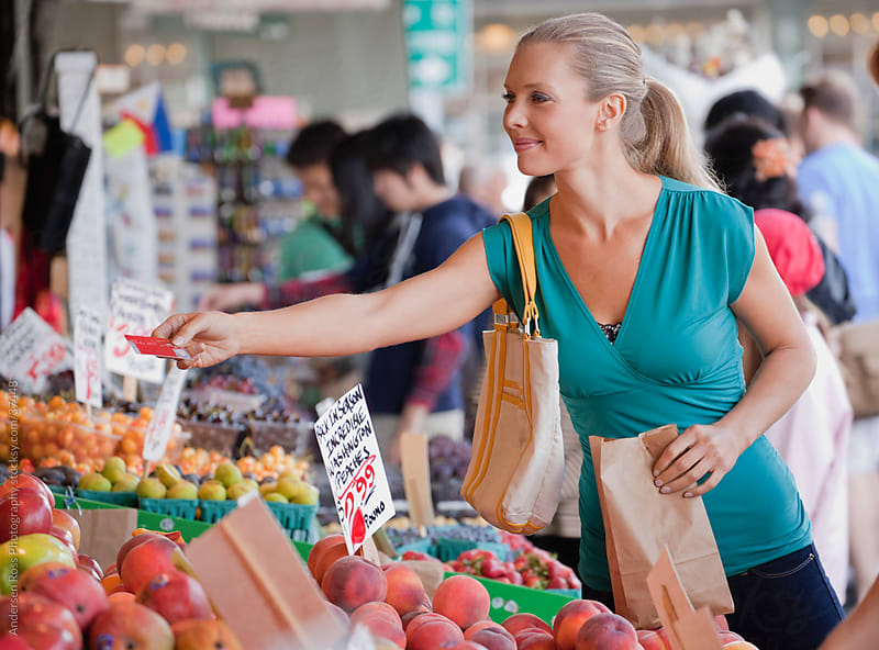Smiling woman shopping for fruit on farmer's market by Andersen Ross Photography for Stocksy United