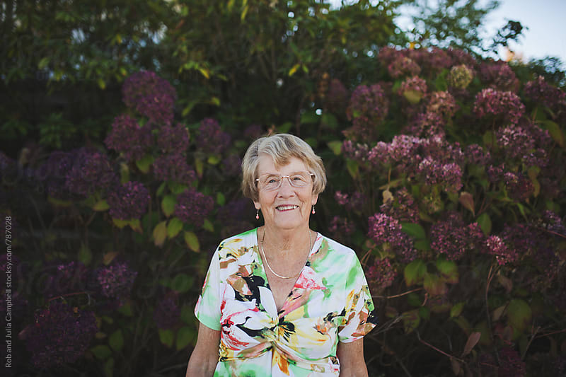 Happy portrait of elderly woman outside near flowers by Rob and Julia Campbell for Stocksy United