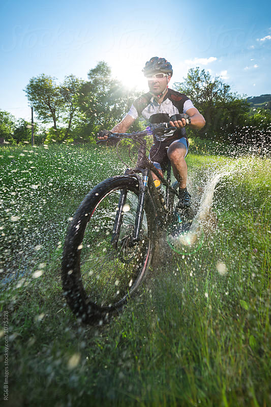 Man riding his mountain bike through a dirty puddle  by RG&B Images for Stocksy United