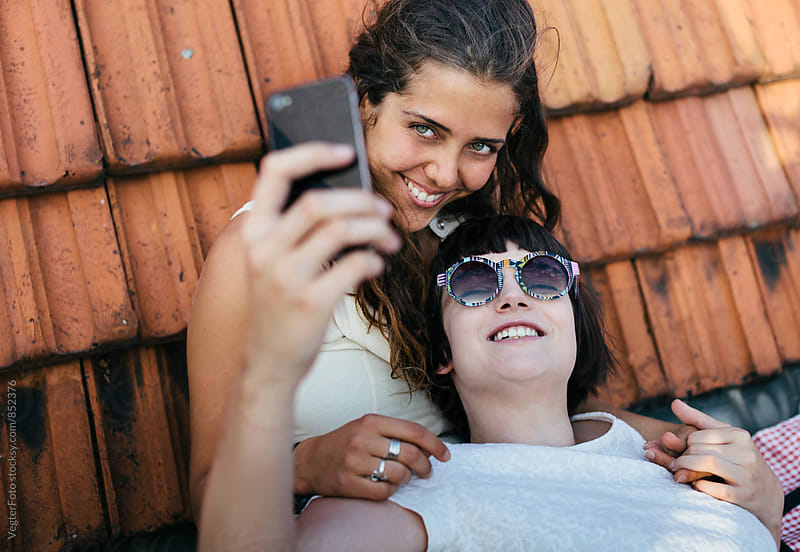 Young women taking selfies together by VegterFoto for Stocksy United
