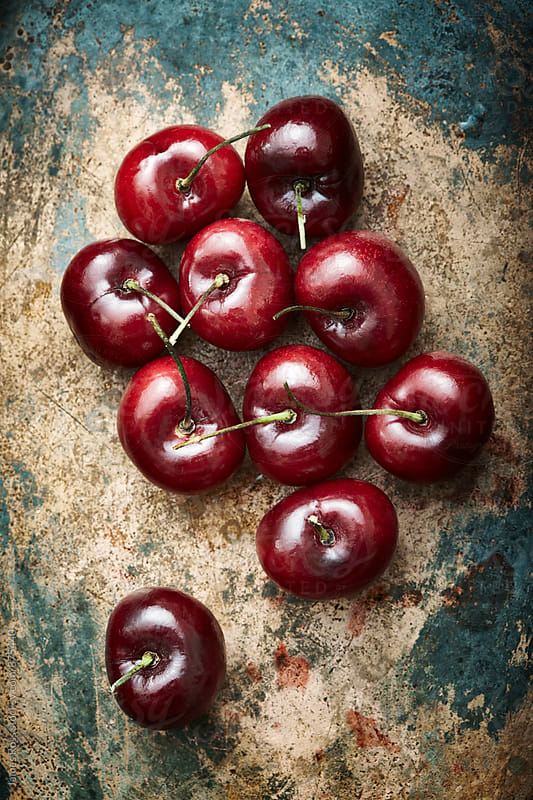 Ten red cherries on a metal kitchen surface by James Ross for Stocksy United
