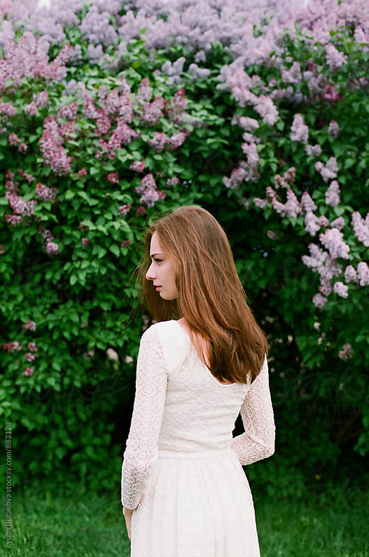 Young woman among lilac blossom by Liubov Burakova for Stocksy United