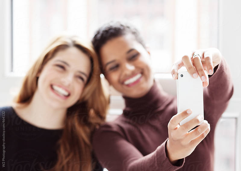 Two friends taking a self portrait selfie with a phone camera by W2 Photography for Stocksy United