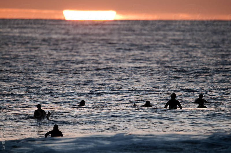 surfers waiting for waves new zealand at sunset. by Jan Bijl for Stocksy United