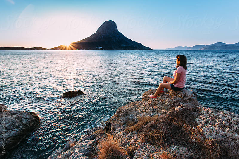 Woman sitting on a rocky outcrop enjoying a sunset view over a calm sea in Kalymnos, Greece by Micky Wiswedel for Stocksy United