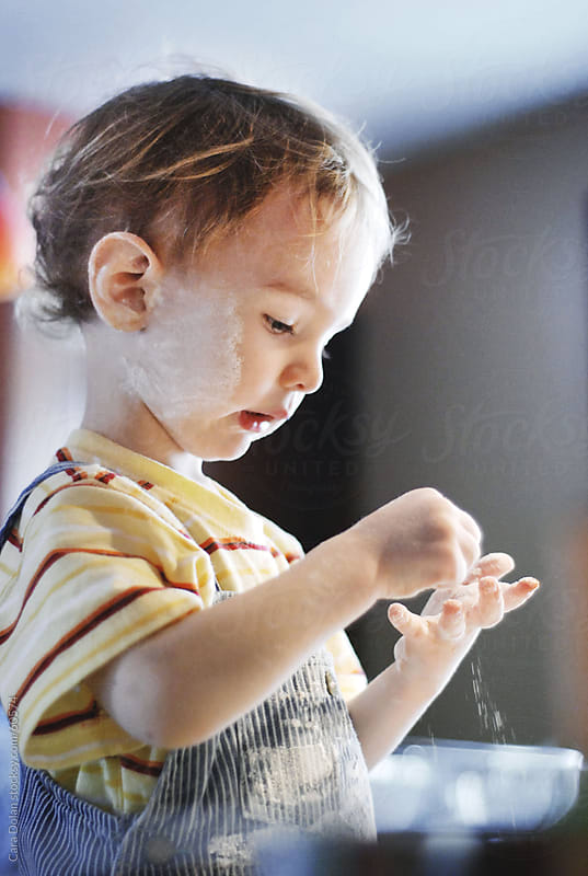 Toddler covered in flour helps bake a cake in the kitchen by Cara Dolan for Stocksy United