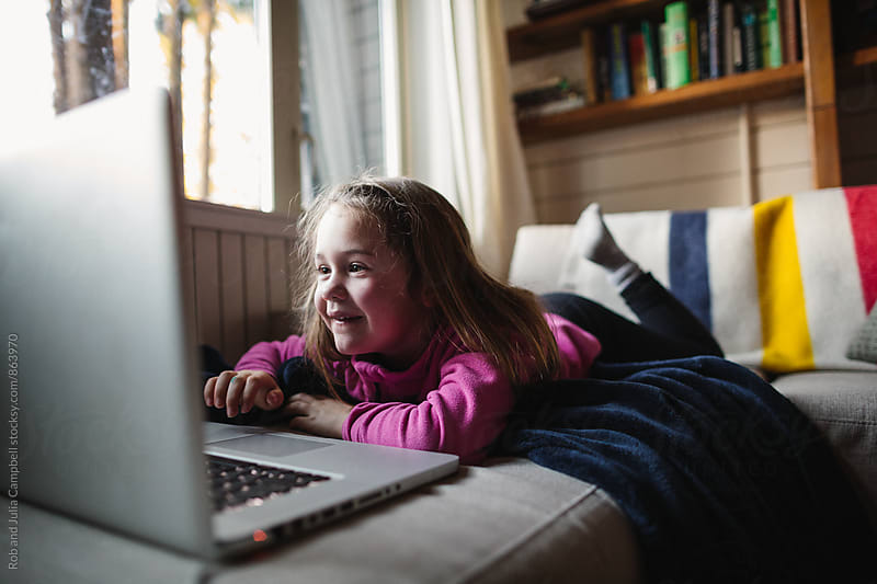 Young girl playing with laptop computer on couch by Rob and Julia Campbell for Stocksy United