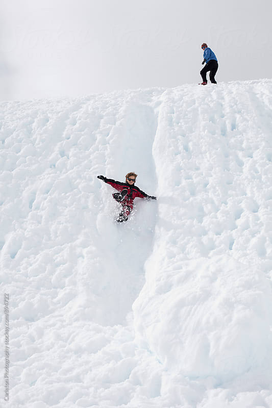 Boy flies down a snowy chute while mom looks on from the top of the hill by Carleton Photography for Stocksy United
