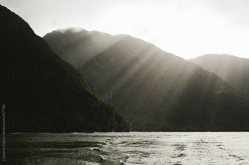 sunlight though clouds on fjord by Cameron Zegers for Stocksy United