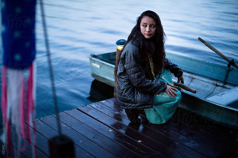 Young girl waits patiently on the dock, holding her row boat  by HOWL for Stocksy United