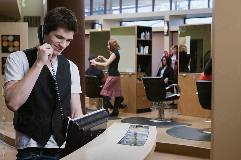 Man talking on phone at reception desk by Andersen Ross Photography for Stocksy United