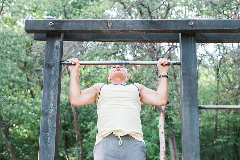 Senior Man Doing Chin-ups in the Park by Aleksandra Jankovic for Stocksy United