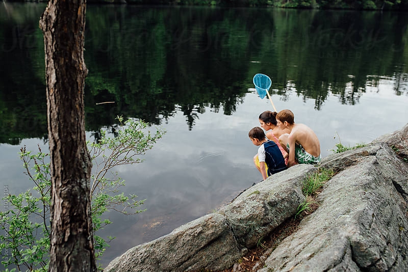 kids sitting on a rock by a lake by Léa Jones for Stocksy United