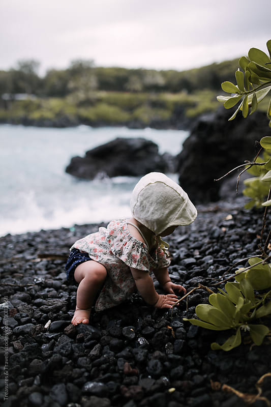 Baby Girl Crawling on a rocky beach by Treasures & Travels for Stocksy United