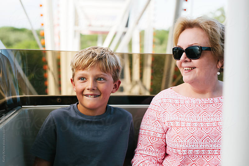 grandmother and grandson ride a ferris wheel by Kelly Knox for Stocksy United