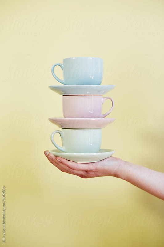 Hand holding cups and saucers by sally anscombe for Stocksy United