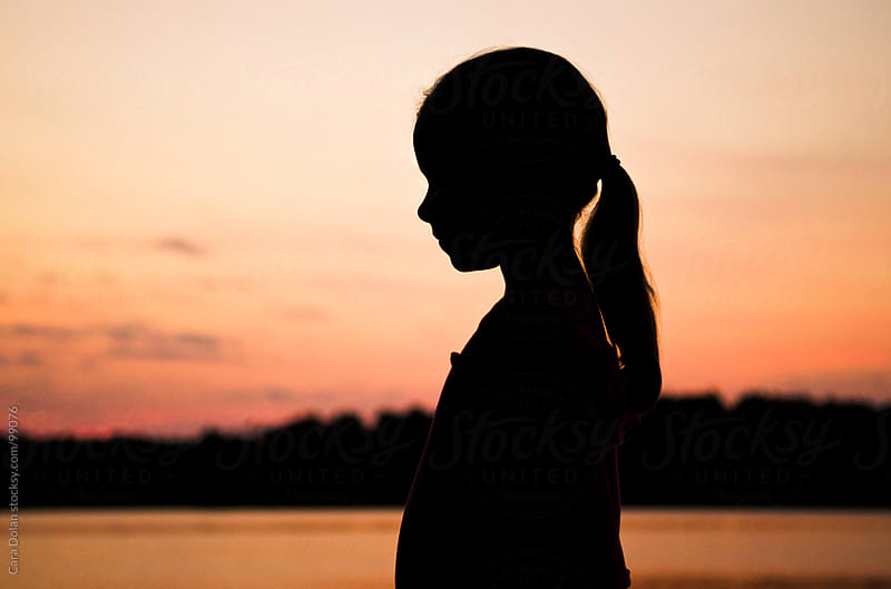 Silhouette of a little girl standing near a lake at sunset ...