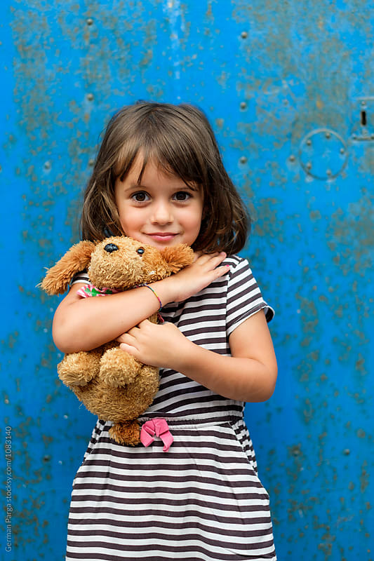 Girl holding her toy with a happy attitude by German Parga for Stocksy United