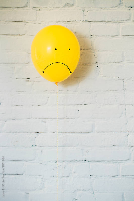 Sad faced yellow balloon looking down by Laura Stolfi for Stocksy United