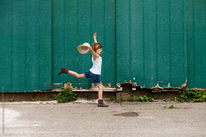 Stylish 8 year old dancing in front of old green wall in summer by Amanda Worrall for Stocksy United
