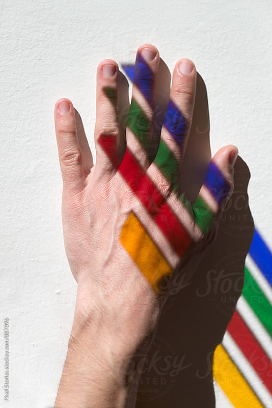Male hand with colorful streaks of light by Pixel Stories for Stocksy United
