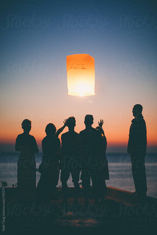 Festival time - friends releasing sky lantern in sunrise  by Nabi Tang for Stocksy United