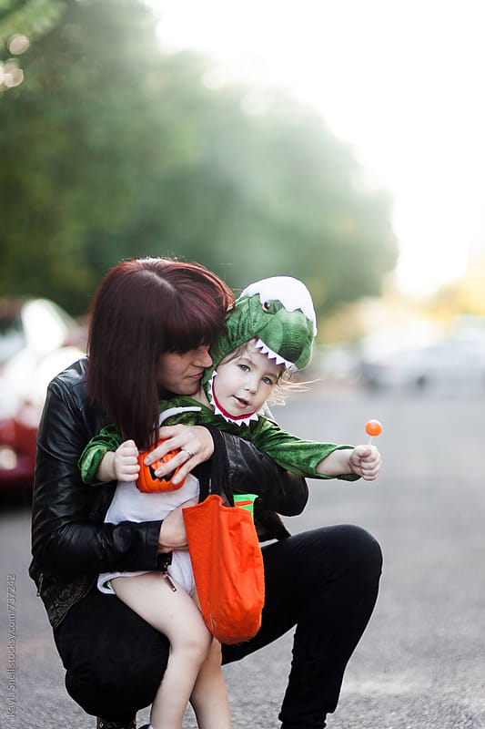 Young boy and his mother trick or treating  by Kayla Snell for Stocksy United