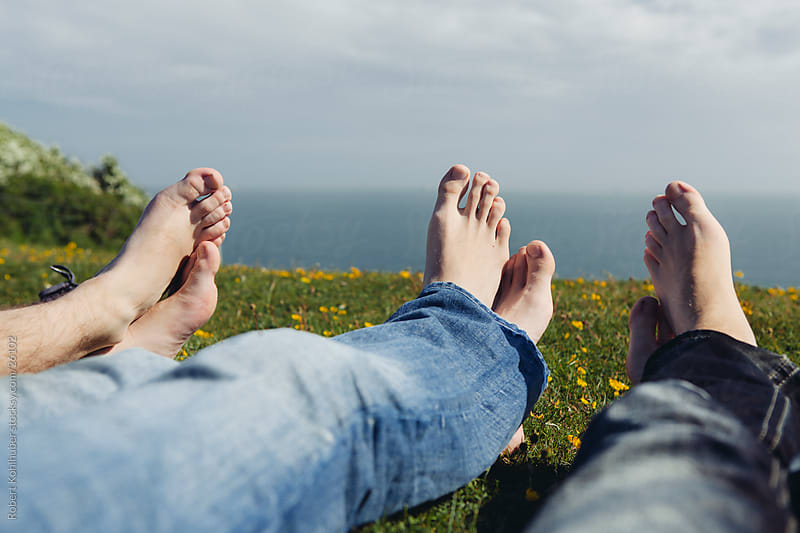 Three pair of feet lying on the coast by Robert Kohlhuber for Stocksy United
