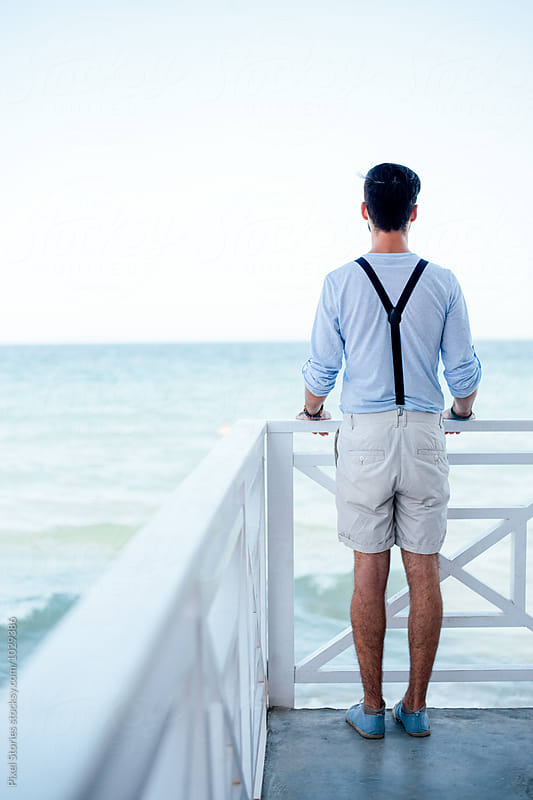 Young man standing on pier by Pixel Stories for Stocksy United